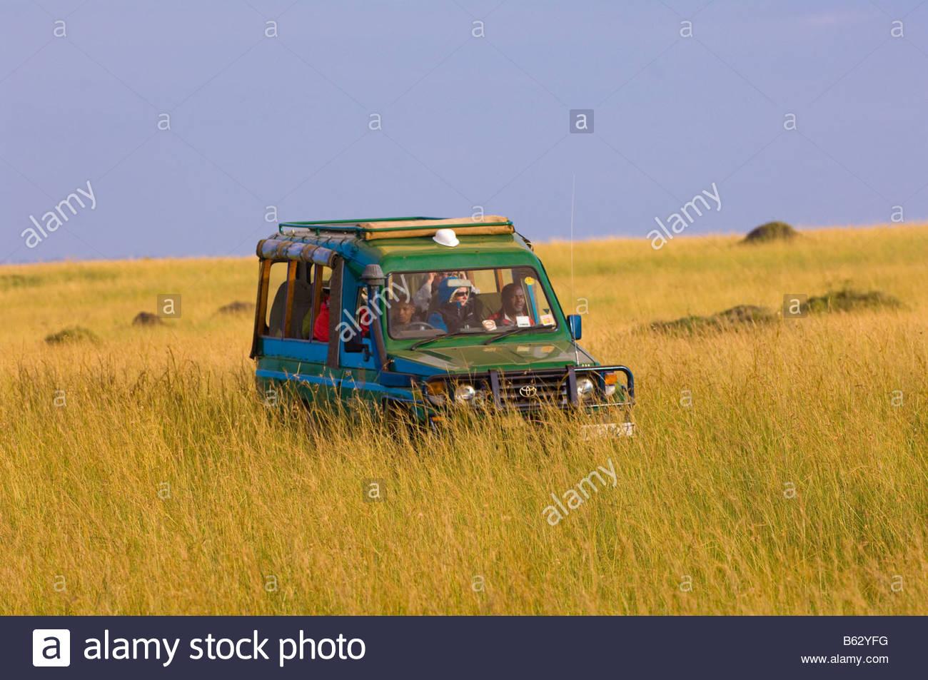 A safari vehicle touring Masai Mara National Reserve Kenya - Stock Image