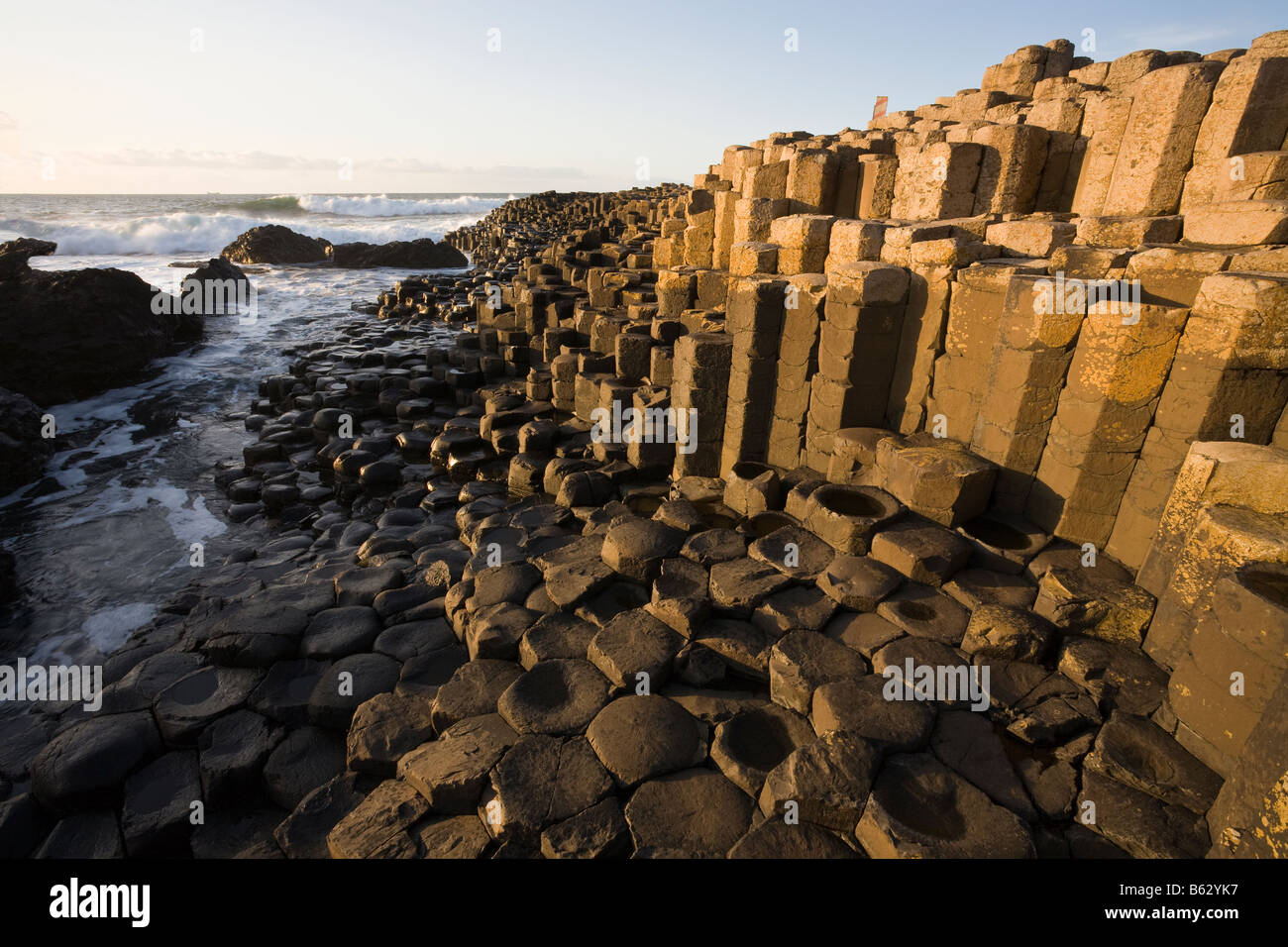 Glowing Causeway: The giant's causeway s unique hexagonally shaped rock columns are a major tourist draw for - Stock Image