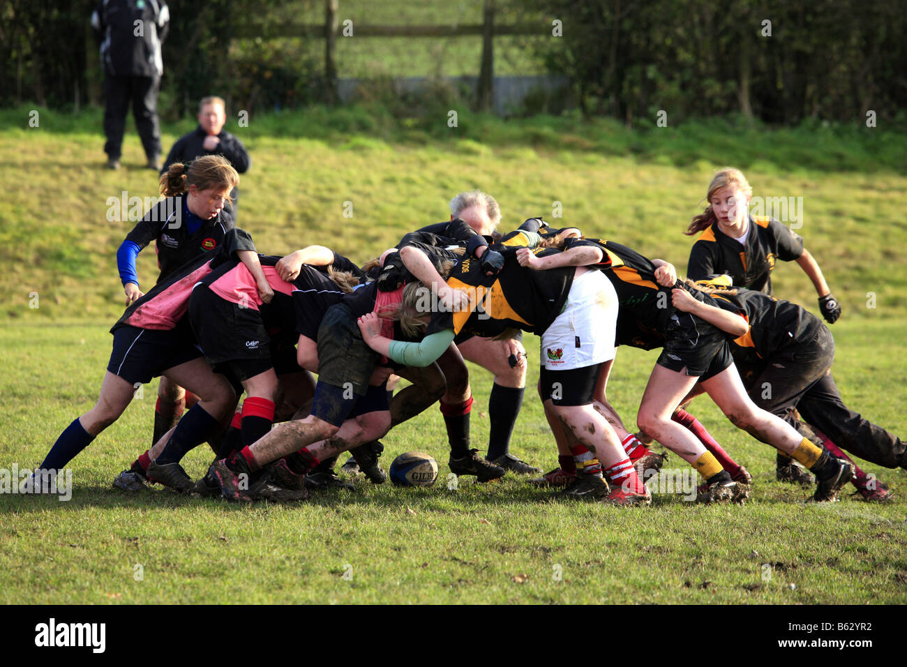 Teenage girls playing Rugby on a cold wet autumn afternoon Stock Photo