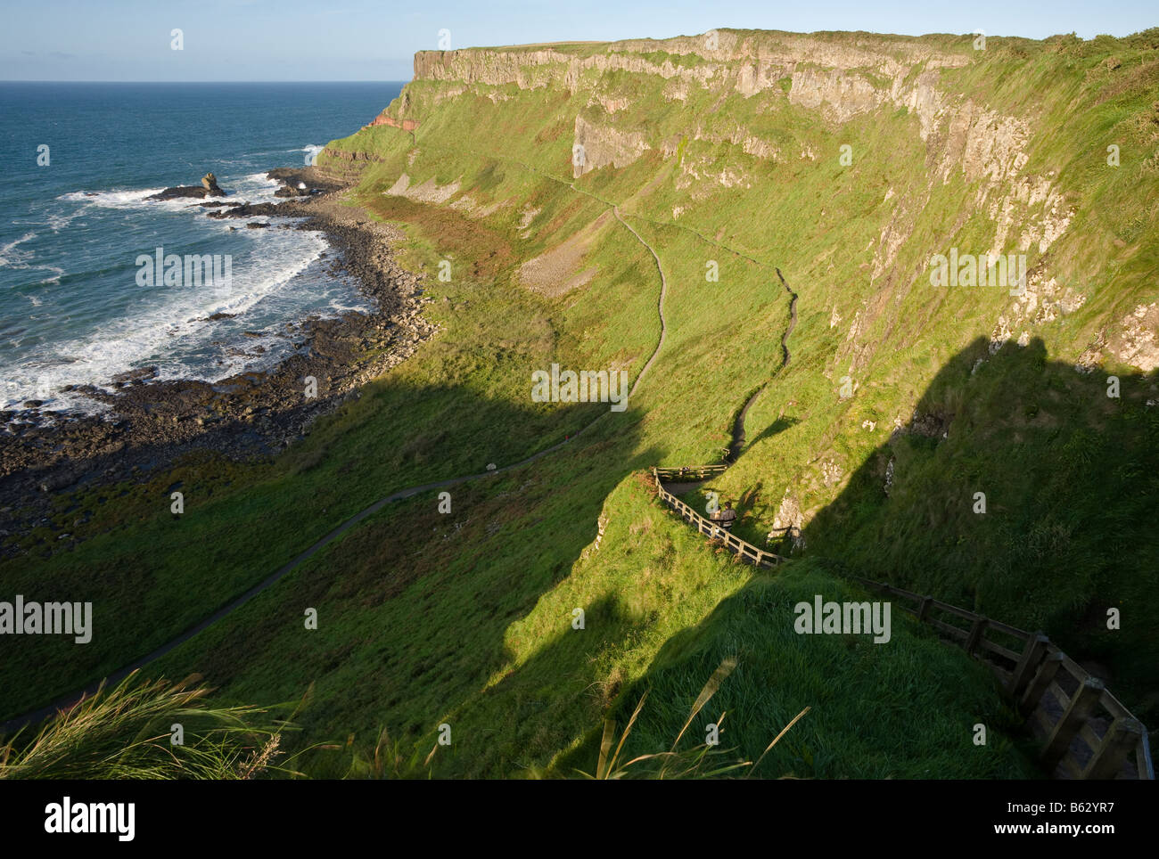 Steps down: The steps down to the causeway from the top of the cliff with the eastern headland beyond. - Stock Image