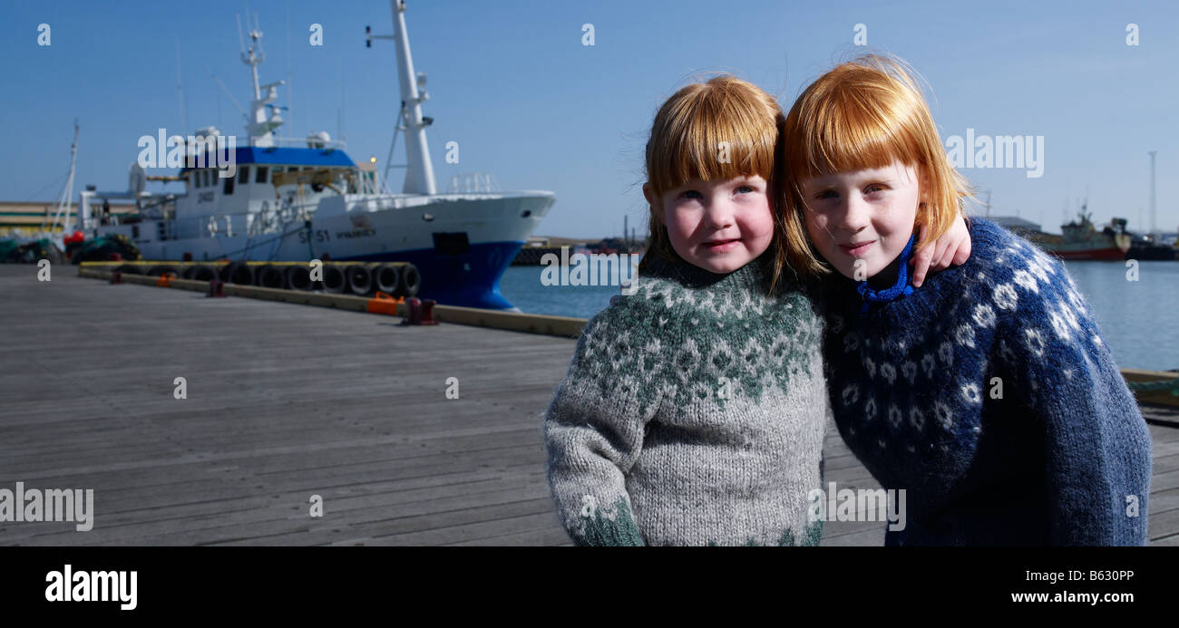 Red headed sisters at harbor,  Eastern Iceland - Stock Image