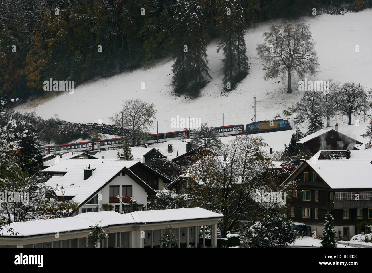 Electric Train in snow leaving Giswil, Switzerland towards the Brunig pass. Stock Photo
