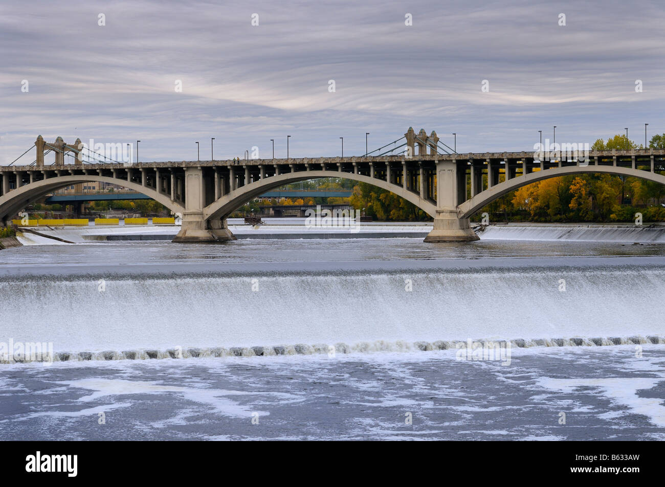 St Anthony Falls on the Mississippi river in Minneapolis with the Third Avenue bridge and inverted wave storm clouds - Stock Image