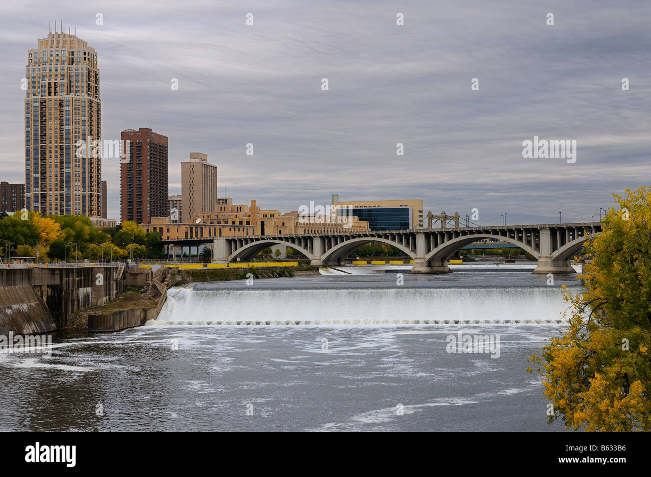 St Anthony Falls on the Mississippi river in Minneapolis with The Carlyle highrise and Third Avenue bridge with - Stock Image