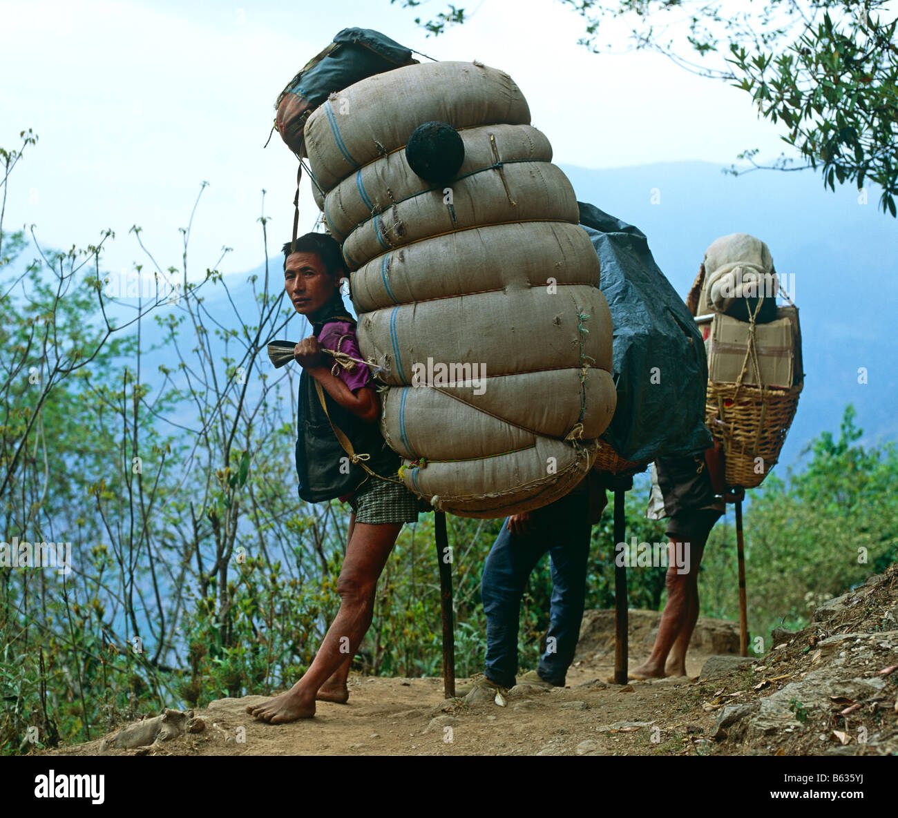 Porters Trekking In The Foothills Of The Annapurna Himalayas Nepal Asia - Stock Image