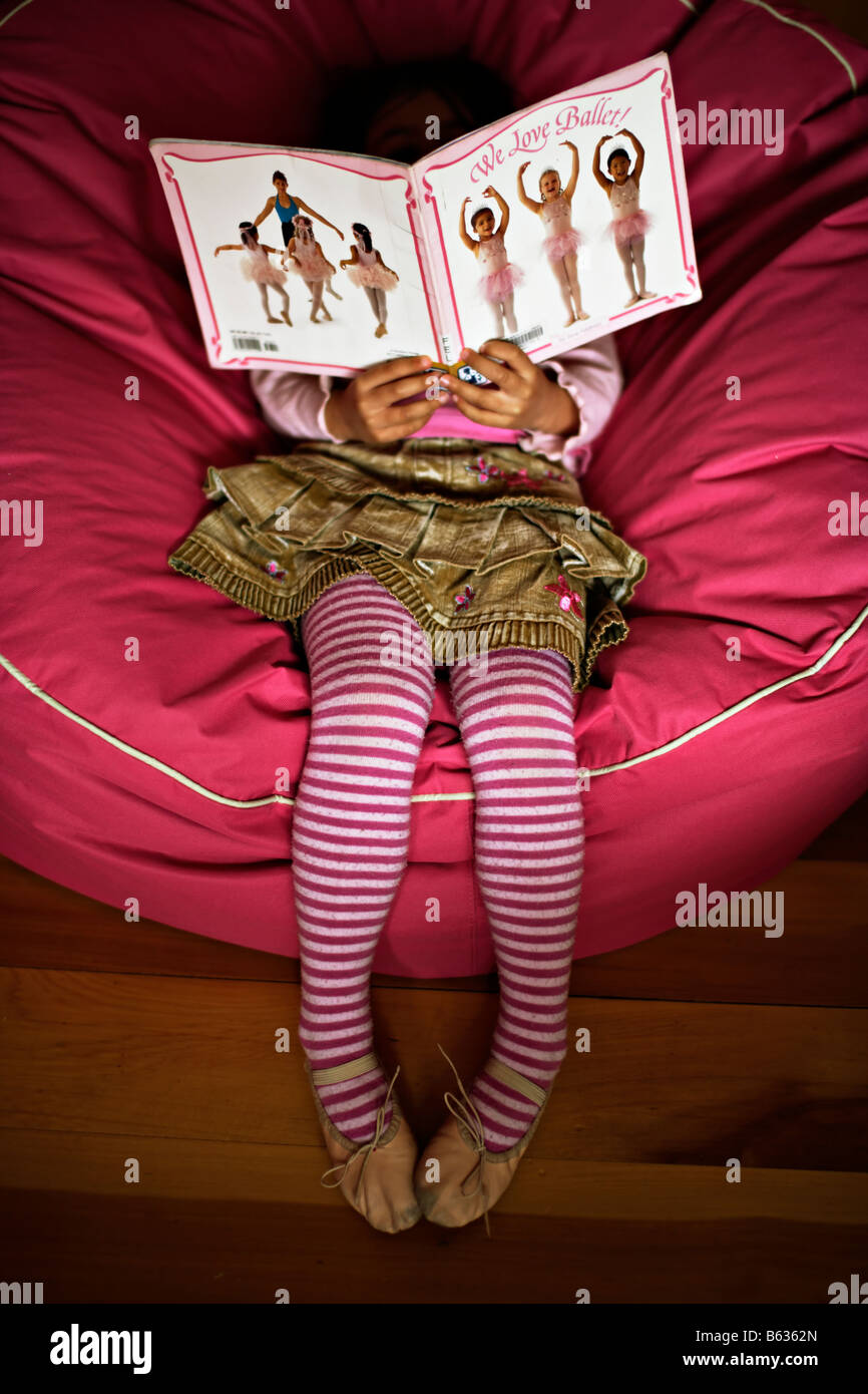 Girl reads ballet book sitting in a bean bag - Stock Image