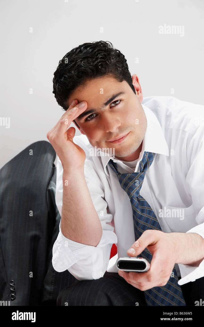 Portrait of a businessman operating a remote control - Stock Image