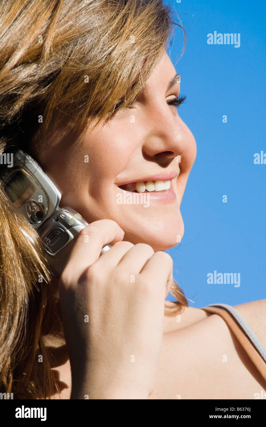 Close-up of a teenage girl talking on a mobile phone and smiling - Stock Image