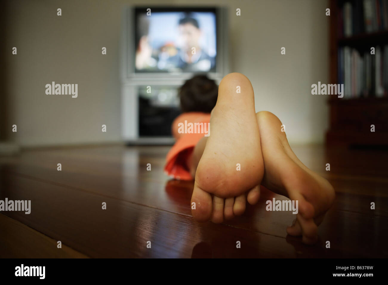 Six year old boy watches television - Stock Image