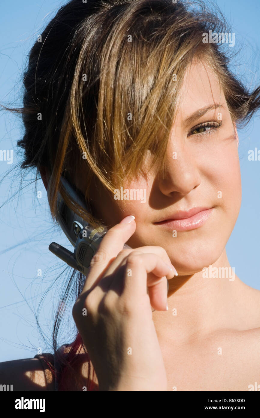 Portrait of a teenage girl talking on a mobile phone - Stock Image