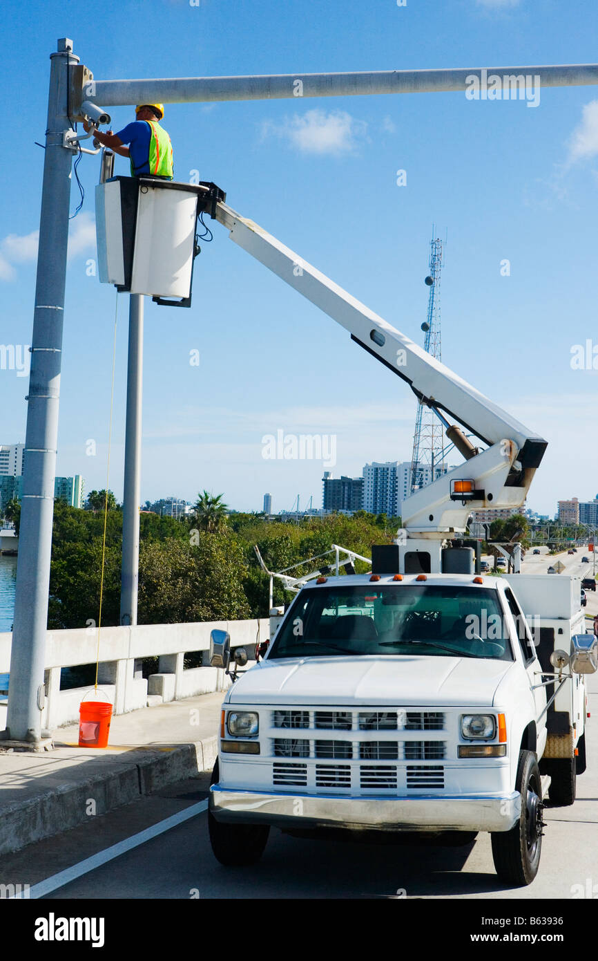 Low angle view of a maintenance engineer on a mobile crane repairing a security camera on a pole - Stock Image
