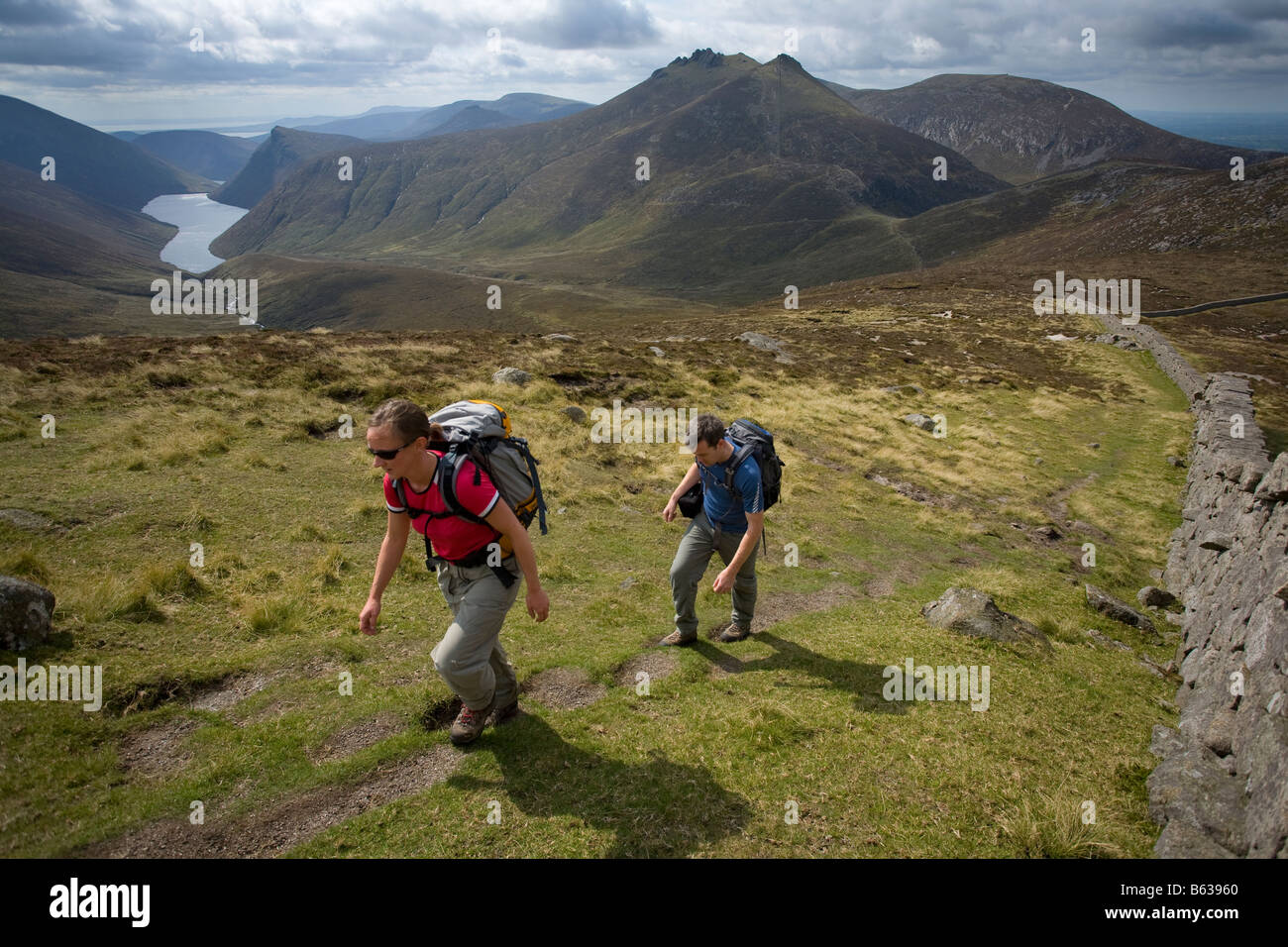 Walkers above the Silent Valley near the summit of Slievenaglogh, Mourne Mountains, County Down, Northern Ireland, - Stock Image