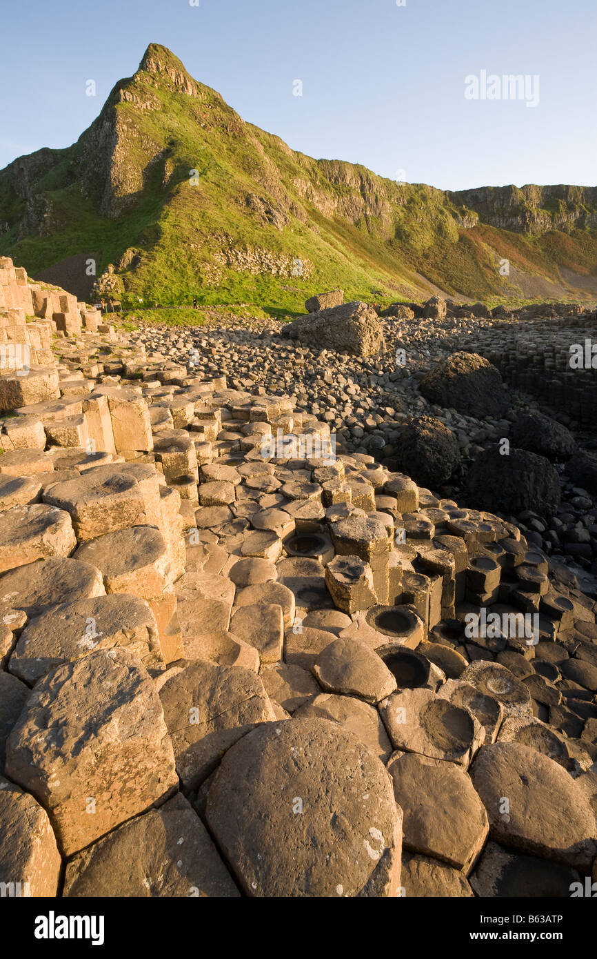 Stepping stones to the peak: Hexagonal pillars of basalt lead the eye toward the sharp peaked hill behind the Causeway Stock Photo