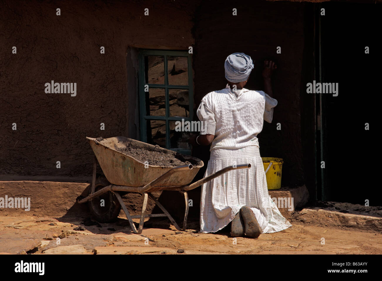 A Basuthu woman plastering the mud wall of a traditional South African Basuthu hut Stock Photo