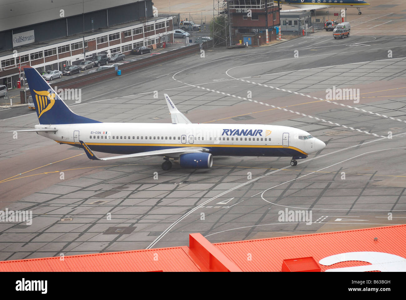 A Ryanair plane taxi's to it's stand at Luton Airport. - Stock Image