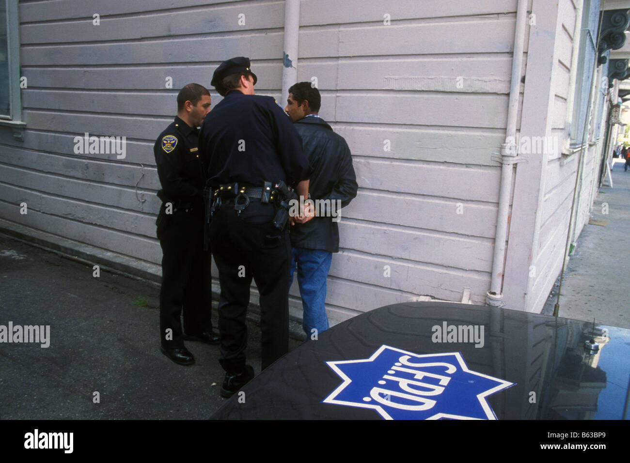 Cops in San Francisco stop and search a man in a side alley - Stock Image
