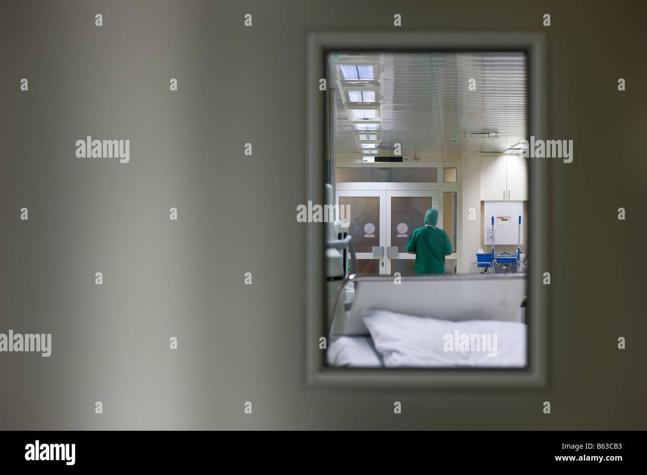 Neurosurgeon thru window entering operating room, Reykjavik Hospital, Iceland - Stock Image