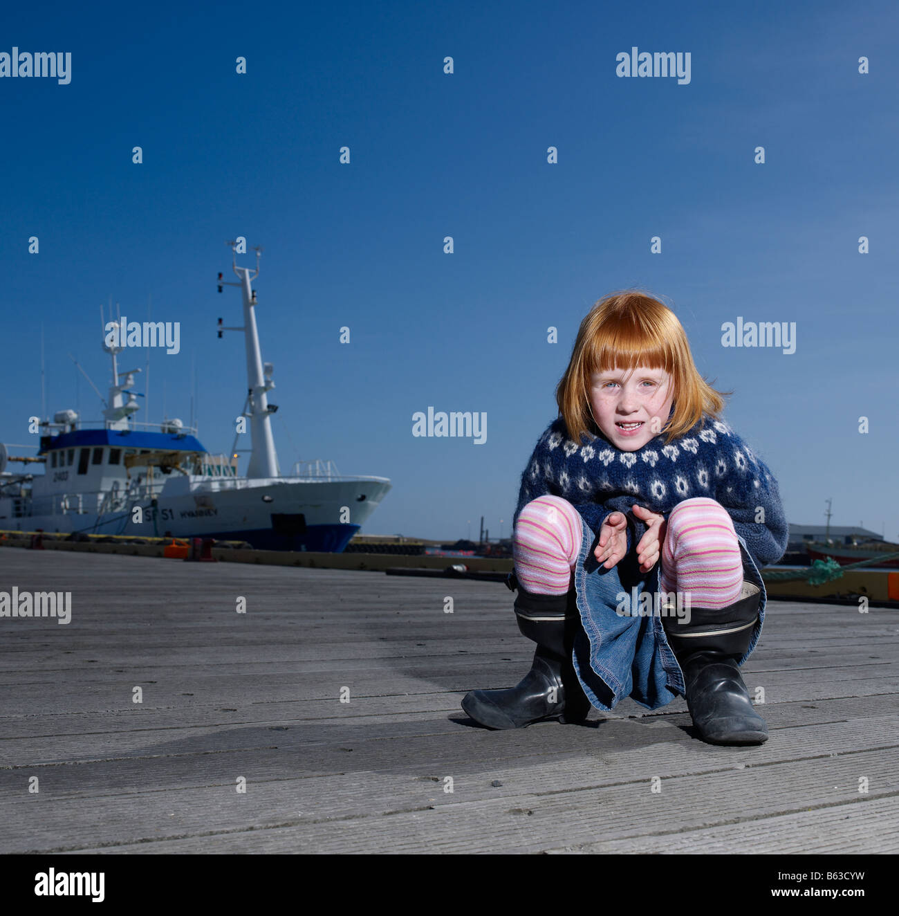 Red headed girl at harbor,  Eastern Iceland - Stock Image