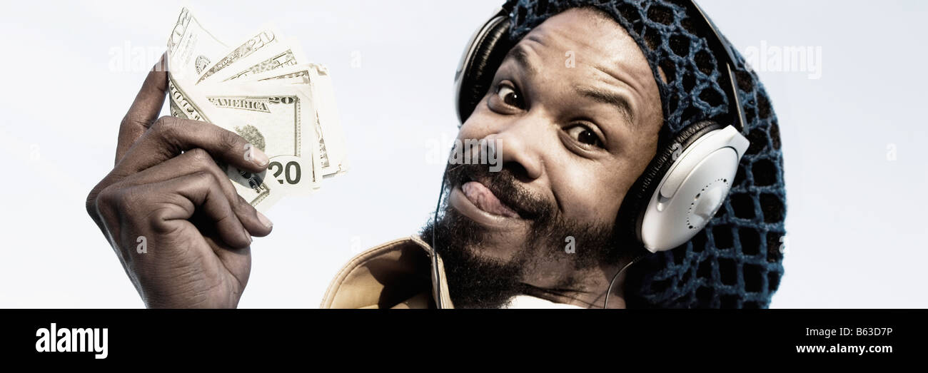 Portrait of a mid adult man listening to music and holding banknotes - Stock Image