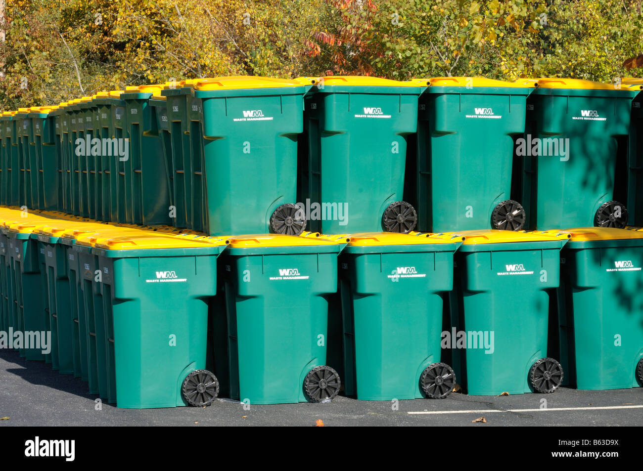 Large group of many new plastic recycling trash barrels or wheelie bins green with yellow lids stacked up in parking Stock Photo