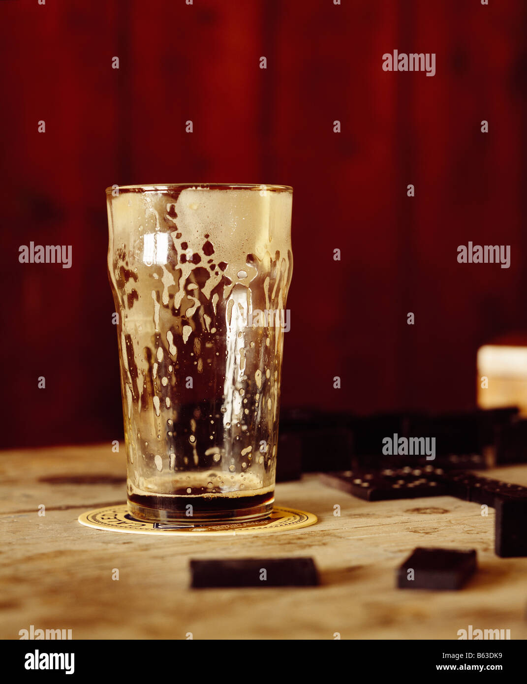a color colour picture of a drained glass of beer, lager, stout or guiness in a bar - Stock Image