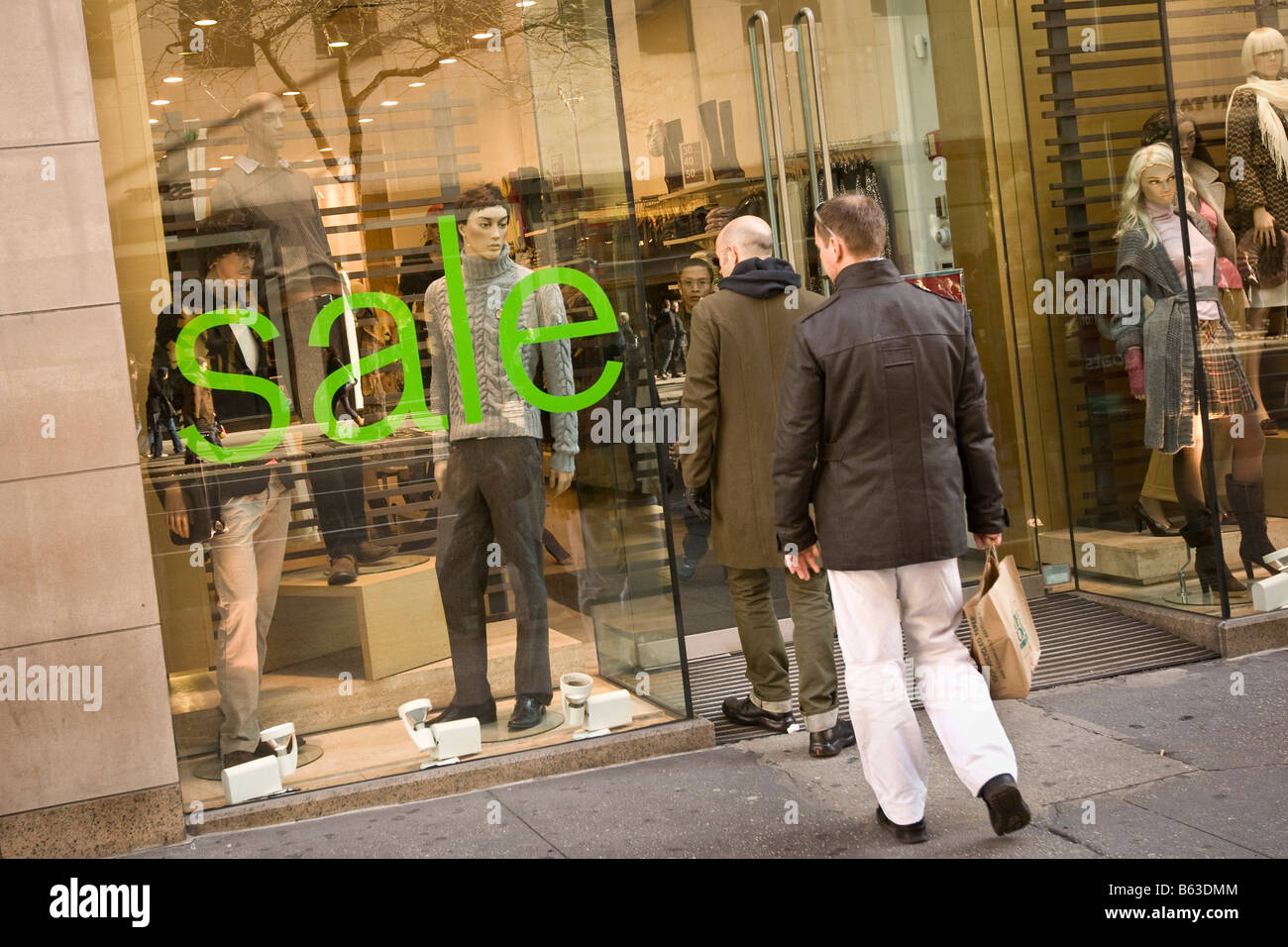 Men enter a clothes store with sale sign in window on 5th Avenue New York USA 23 November 2008 - Stock Image