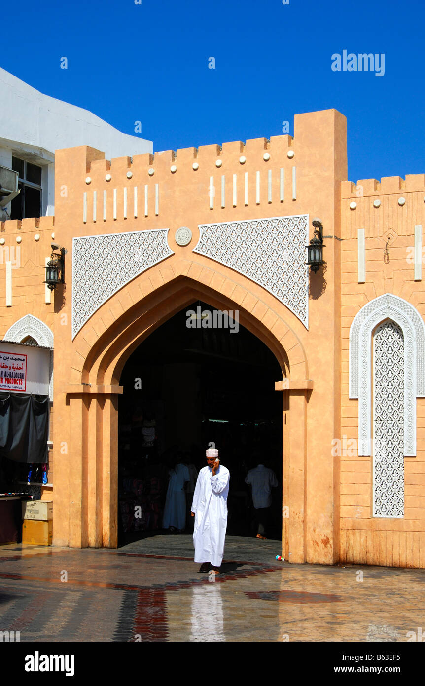 Local man in the national dress makes a call at the entrance gate to the Mutrah Souq, Muscat, Sultanate of Oman - Stock Image