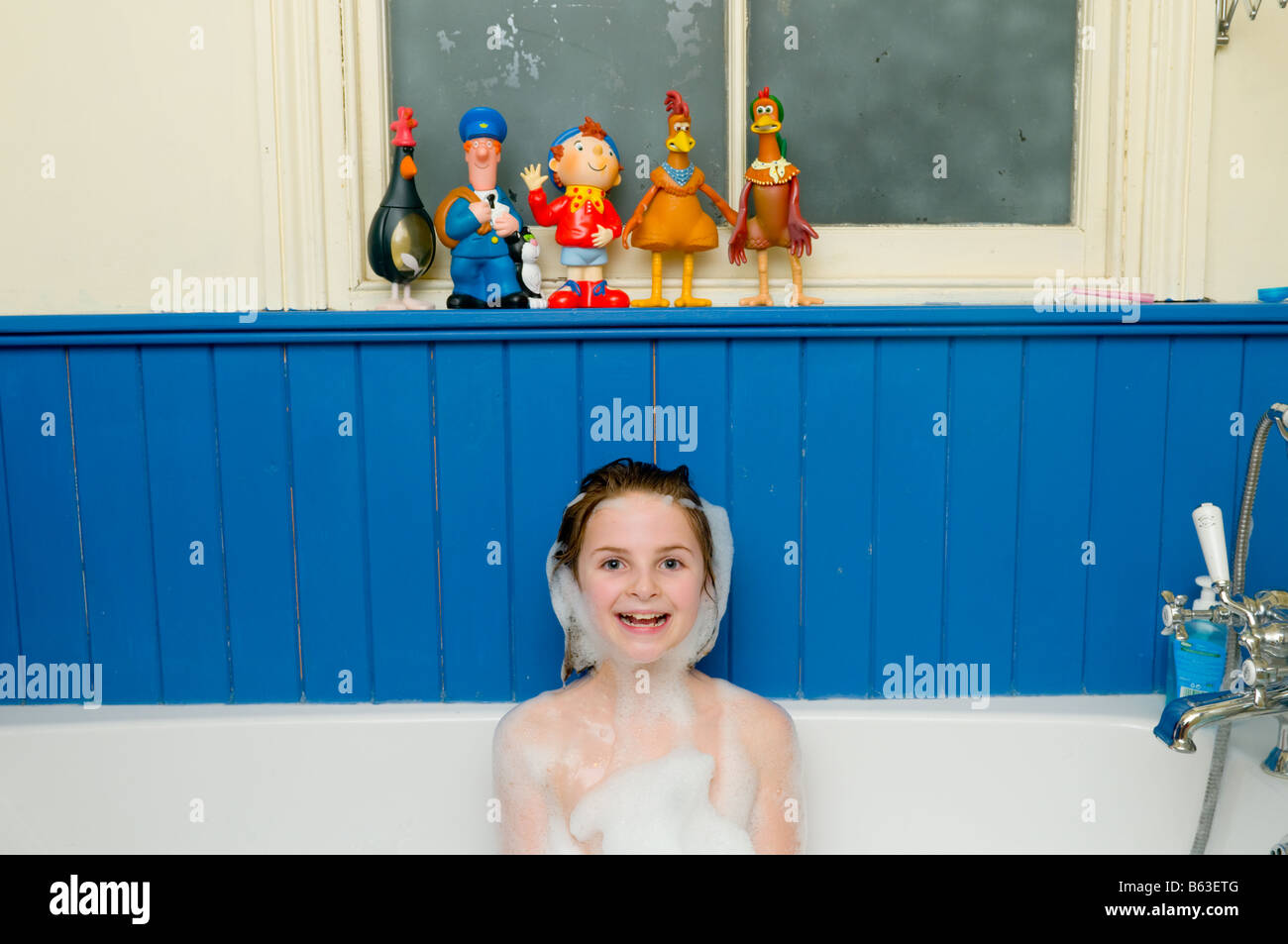 Ten year old girl in the bath looking happy smiling cheeky and cute with soapy bubbles like a beard around her face, - Stock Image