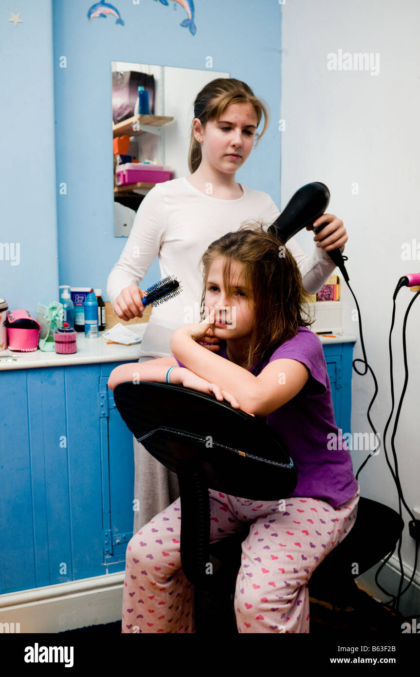 Teenage girl drying her ten year old sisters hair with an electric hairdrier in their bedroom, UK - Stock Image