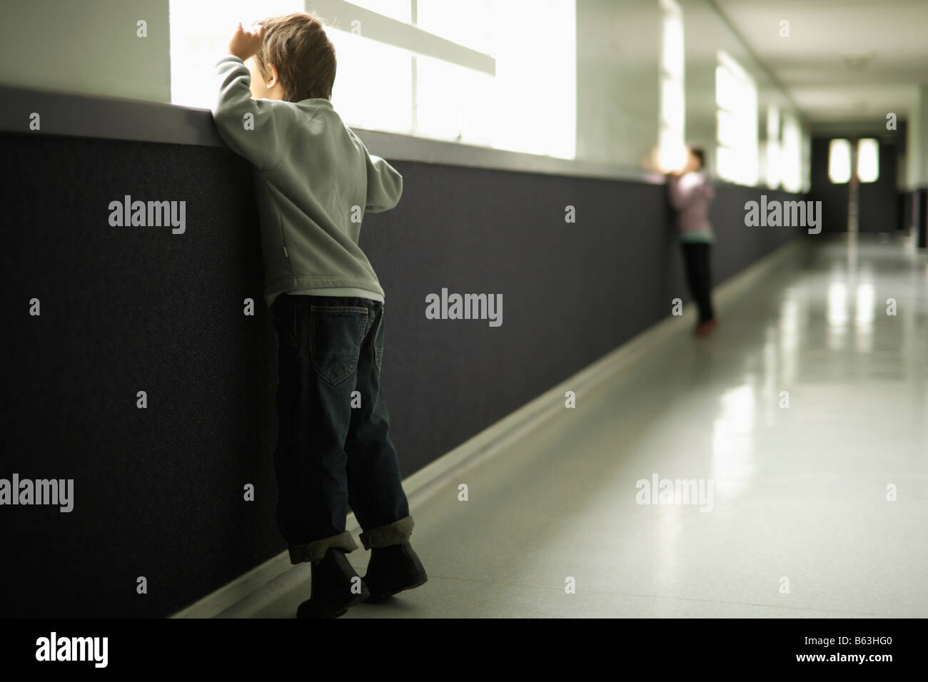 Boy aged six girl aged five stand in school corridor looking out window - Stock Image