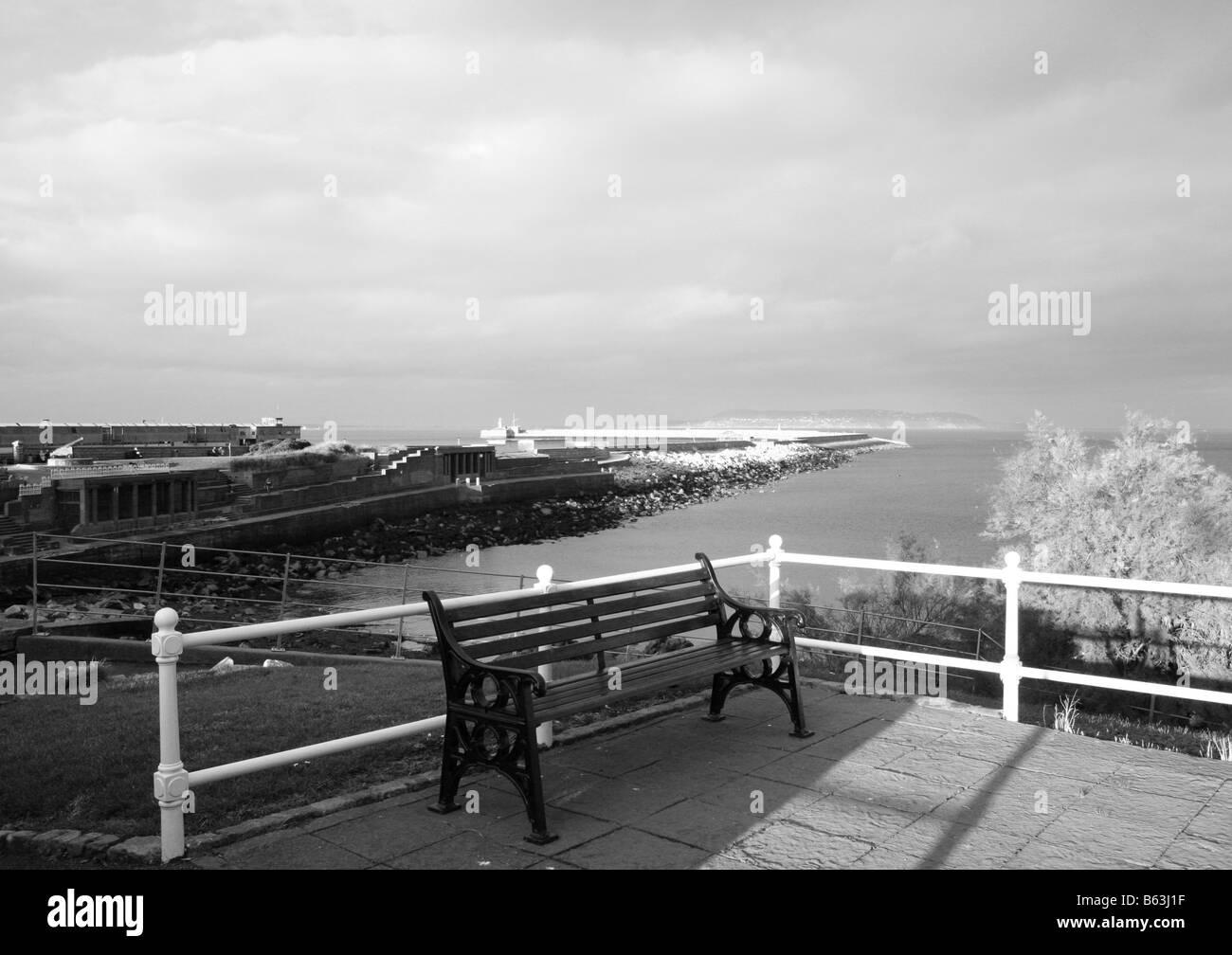 East Pier DunLaoghaire Pier Co Dublin CoDublin County Ireland Dun Laoghaire Eire Bench Black and White - Stock Image