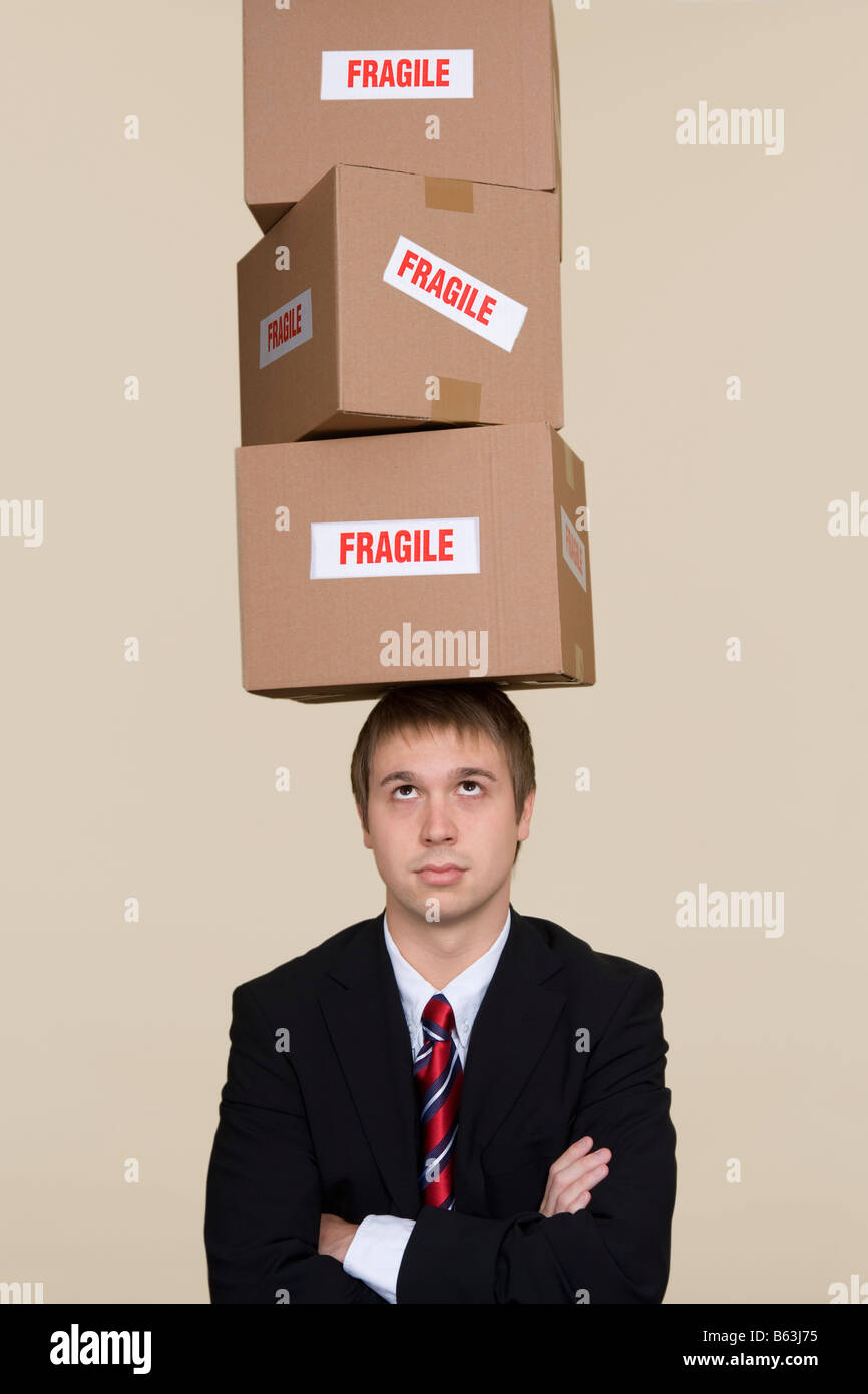 Young businessman balancing boxes on head - Stock Image