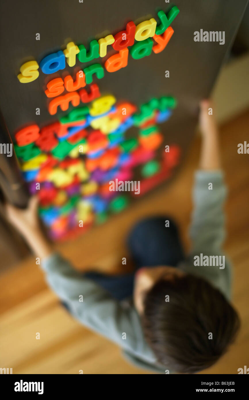 Six year old boy spells days with fridge magnets - Stock Image