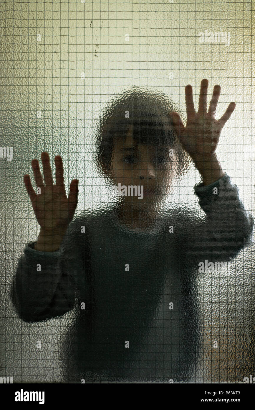 Six year old boy behind glass - Stock Image