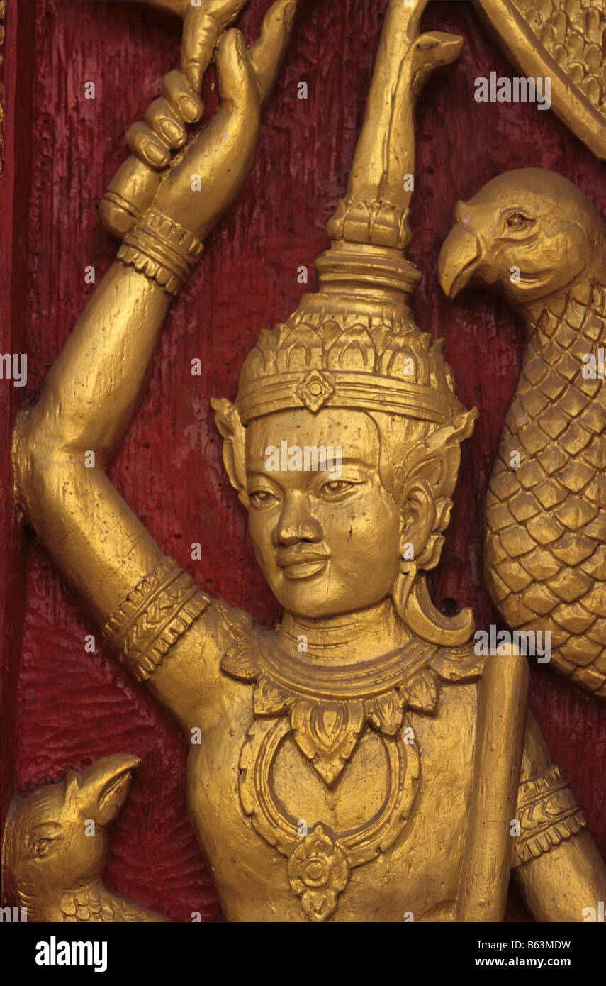 A carved and gilded Loatian figure or Buddhist diety on the doors of Wat That Luang Neua temple, Vientiane, Loas - Stock Image