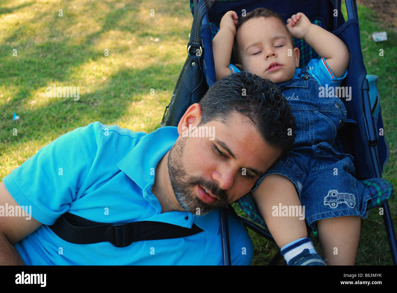 A father sleeping with his toddler son - Stock Image