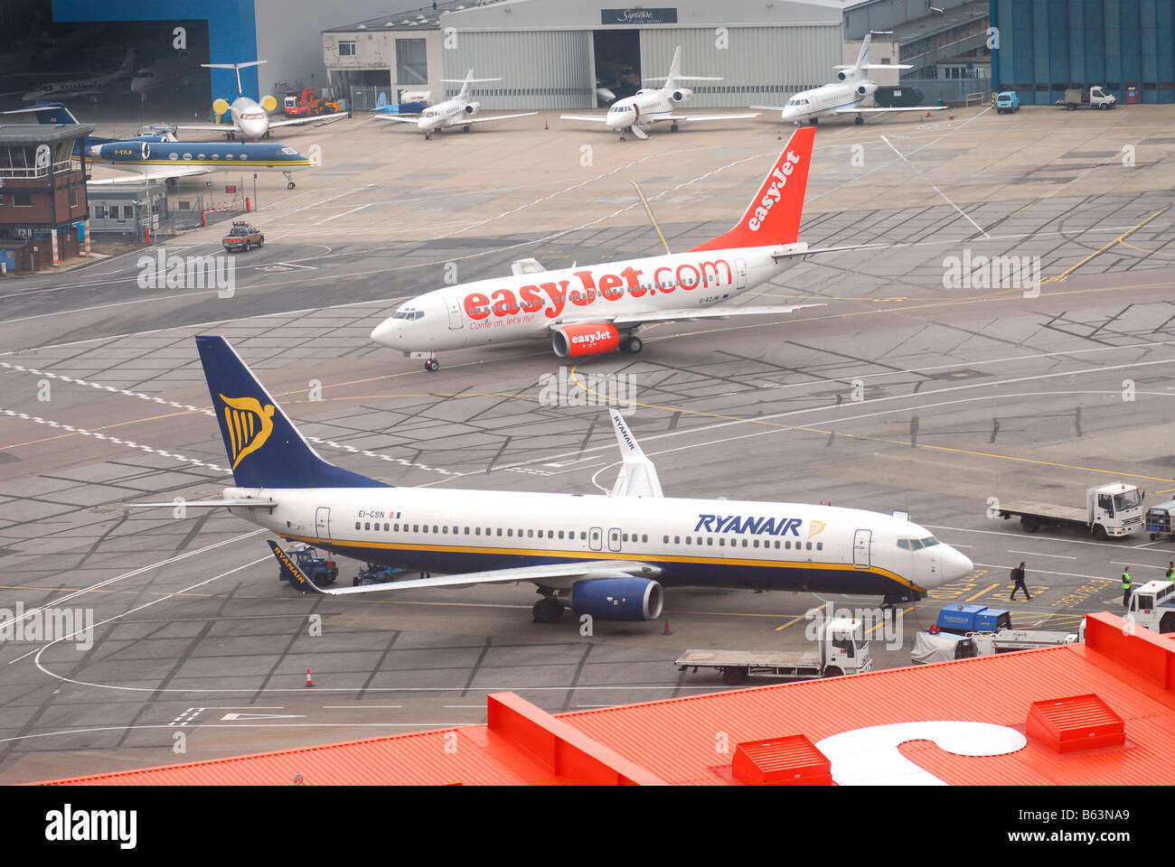 Rivals. easyjet and Ryanair planes pass each other at Luton Airport. - Stock Image