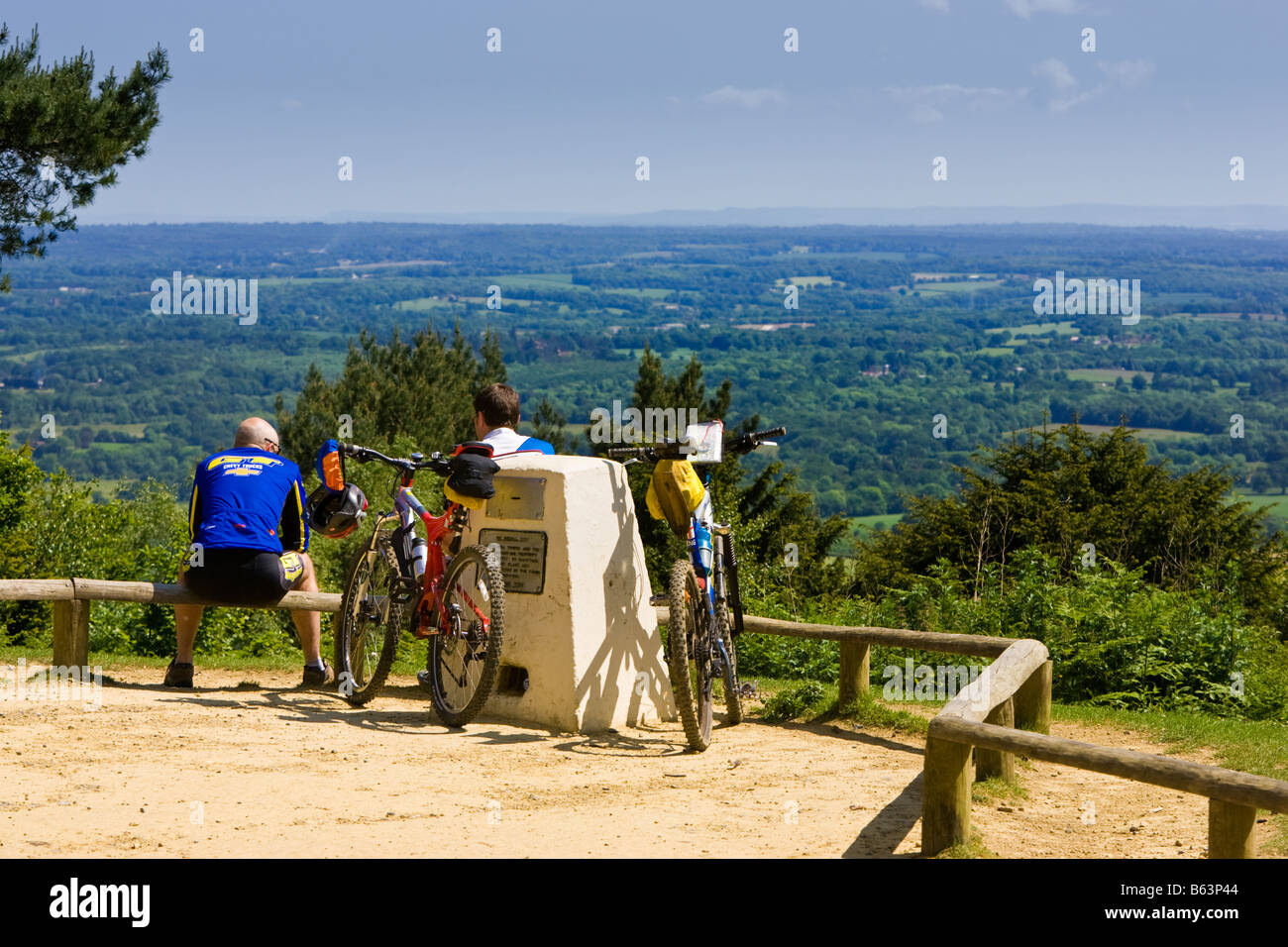 Two cyclists enjoying the views over the Weald and South Downs countryside at the top of Leith Hill, Surrey, England - Stock Image