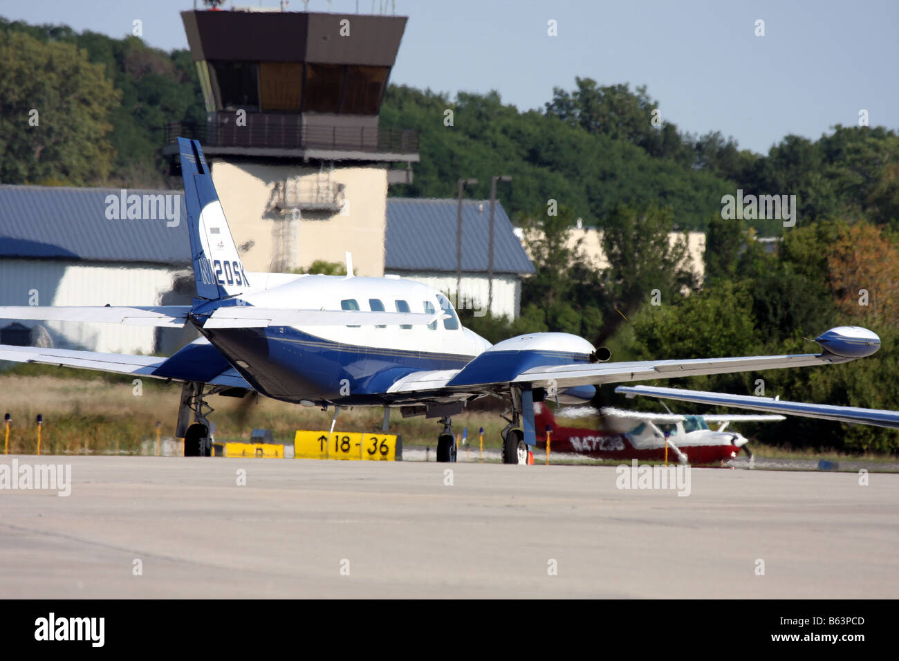 A twin engine Piper taxing on the runway after landing at Crites Airfield in Waukesha Wisconsin Control tower in - Stock Image
