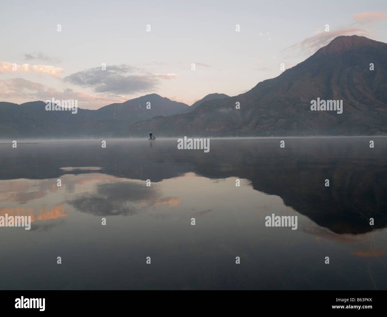 A fishermen and reflection on the surface of lake - Stock Image