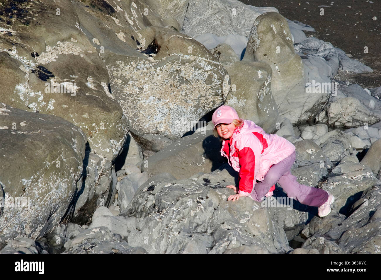 A little girl scrambles up rock at Hole in the Wall Rialto Beach Olympic National Park Washington - Stock Image