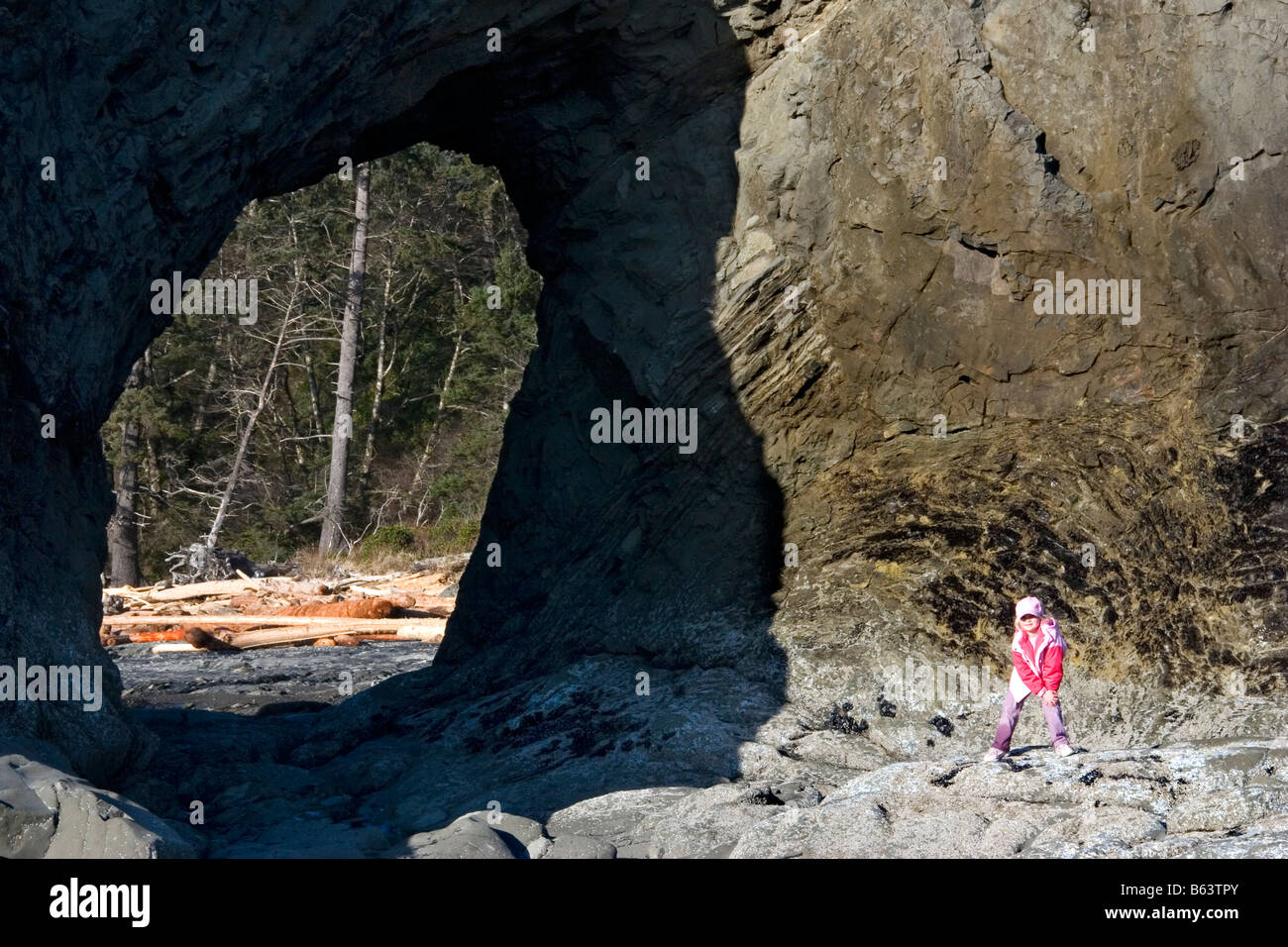 A young hiker plays on the rocks at Hole in the Wall Rialto Beach Olympic National Park Washington - Stock Image