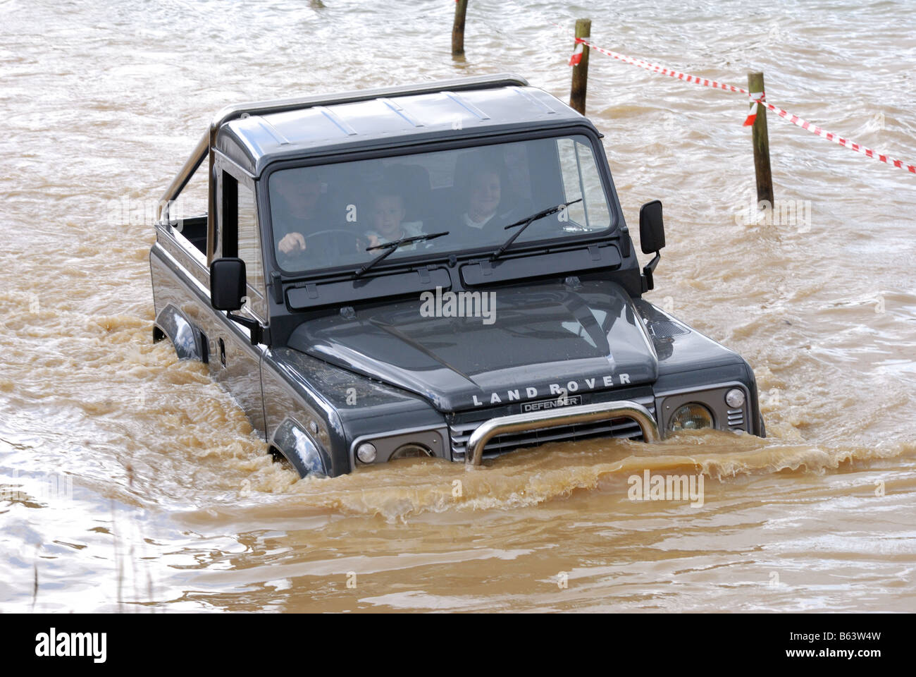 Green short wheelbase Land Rover Defender with anti roll bar in the water at Billing drive around 4WD four wheel - Stock Image