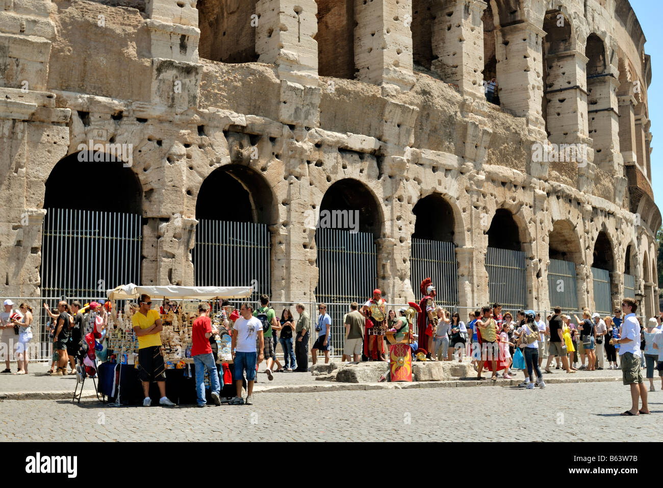 690adc982 A street trader sell fake brand goods to tourists by the Colosseum and Roman  soldiers pose