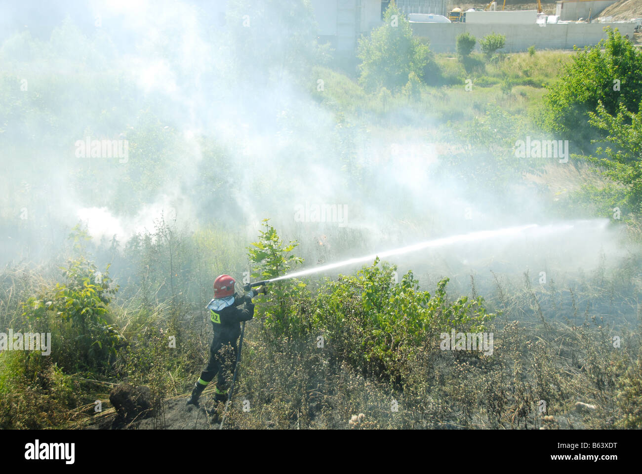 Firefighters using a hose reel jet on a heath fire - Stock Image