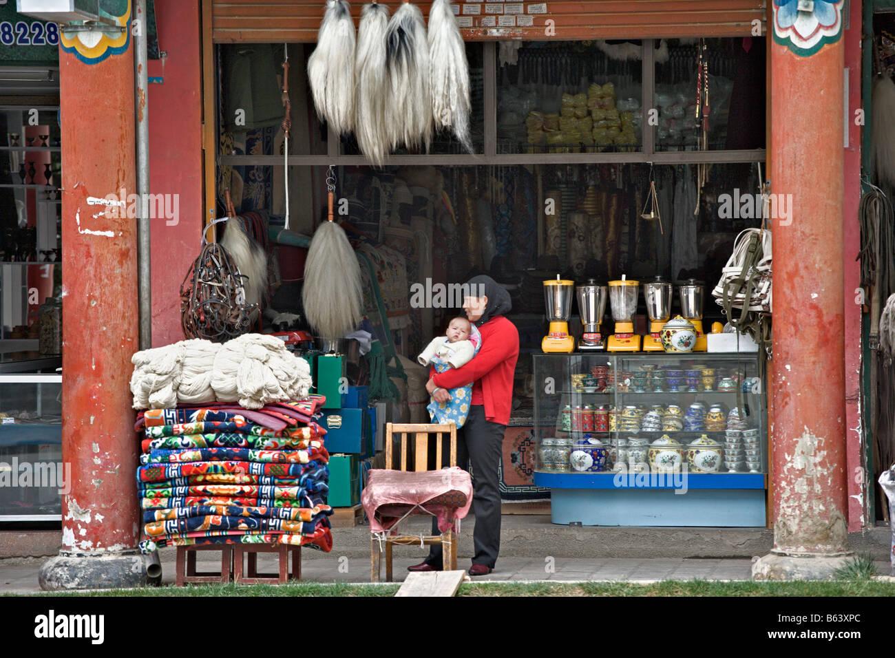Tibetan storefront with mother baby. Store sells horse halters, rugs, blenders, et cetera, Zhongdian (Shangri-La), Stock Photo