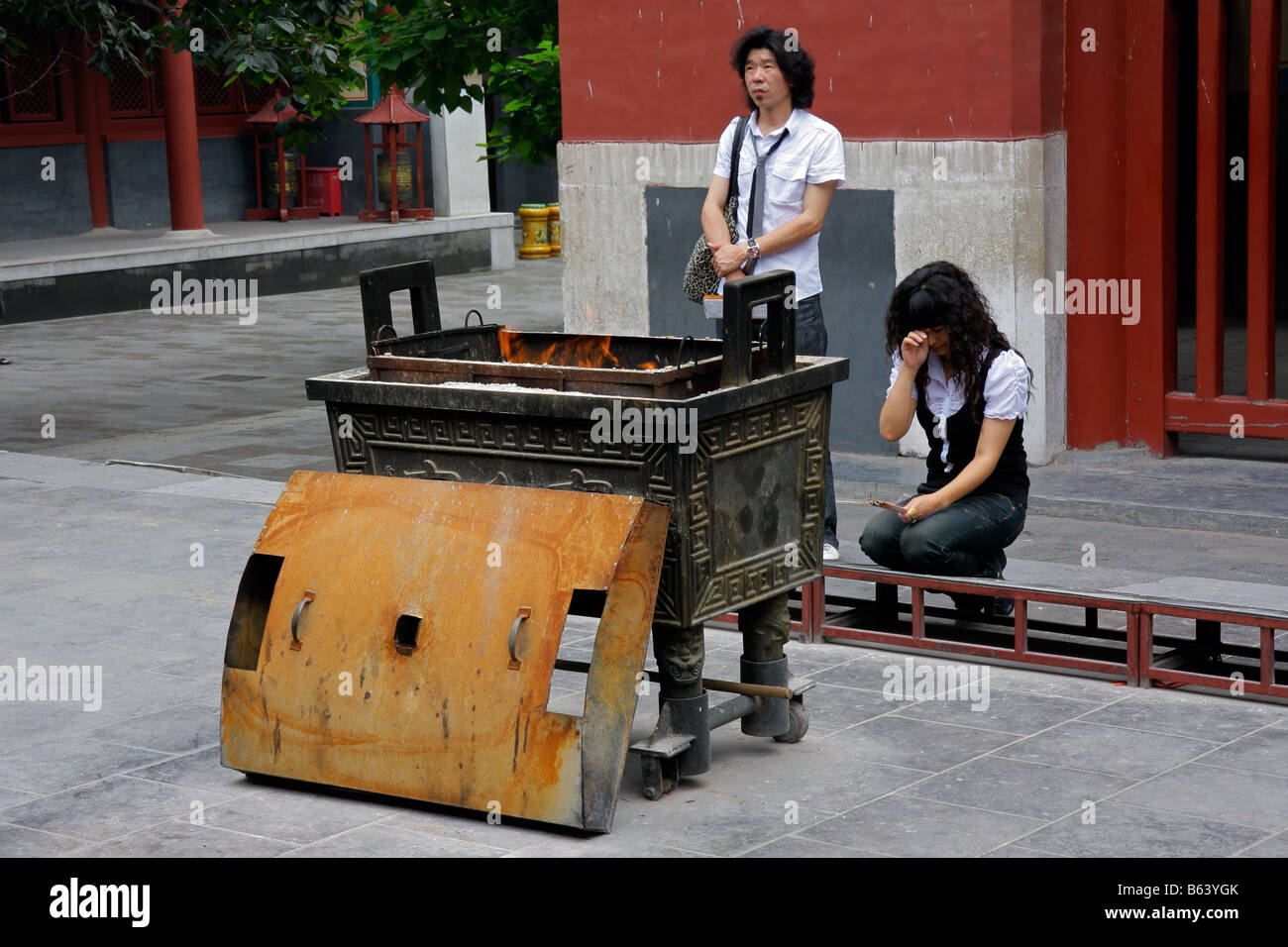 Chinese man and woman in religious offering, burning incense sticks in the YongHeGong lama temple in Beijing, China Stock Photo