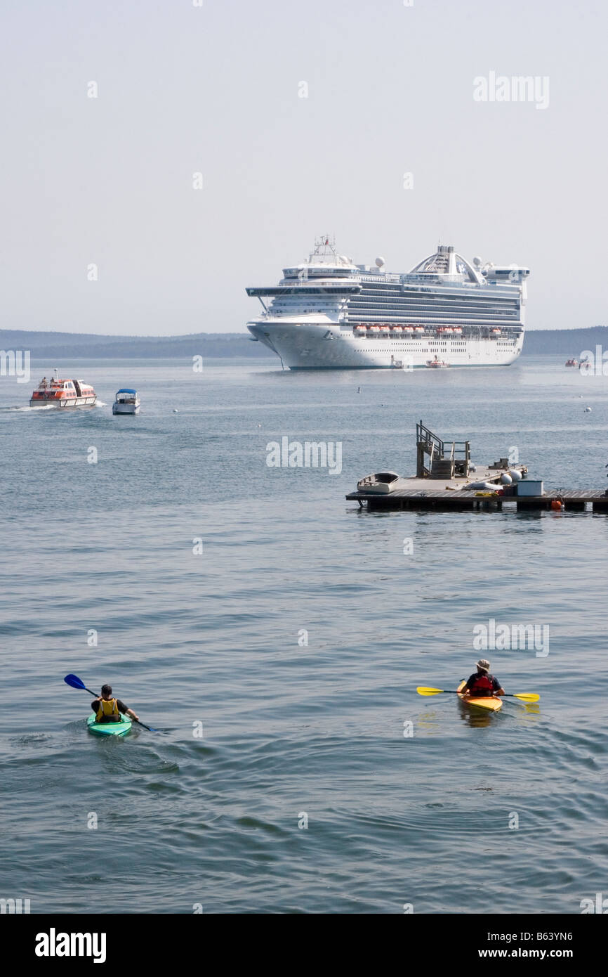 Cruise ship anchored near Bar Harbor, Maine. Tourists are brought to the ship in small shuttle boats as two kayakers - Stock Image