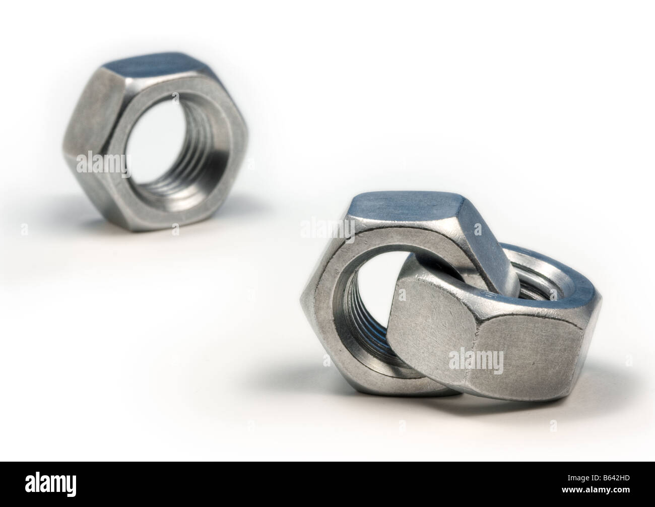 Single nut looking at a couple tied together. Metaphor for jealousy or infidelity - Stock Image