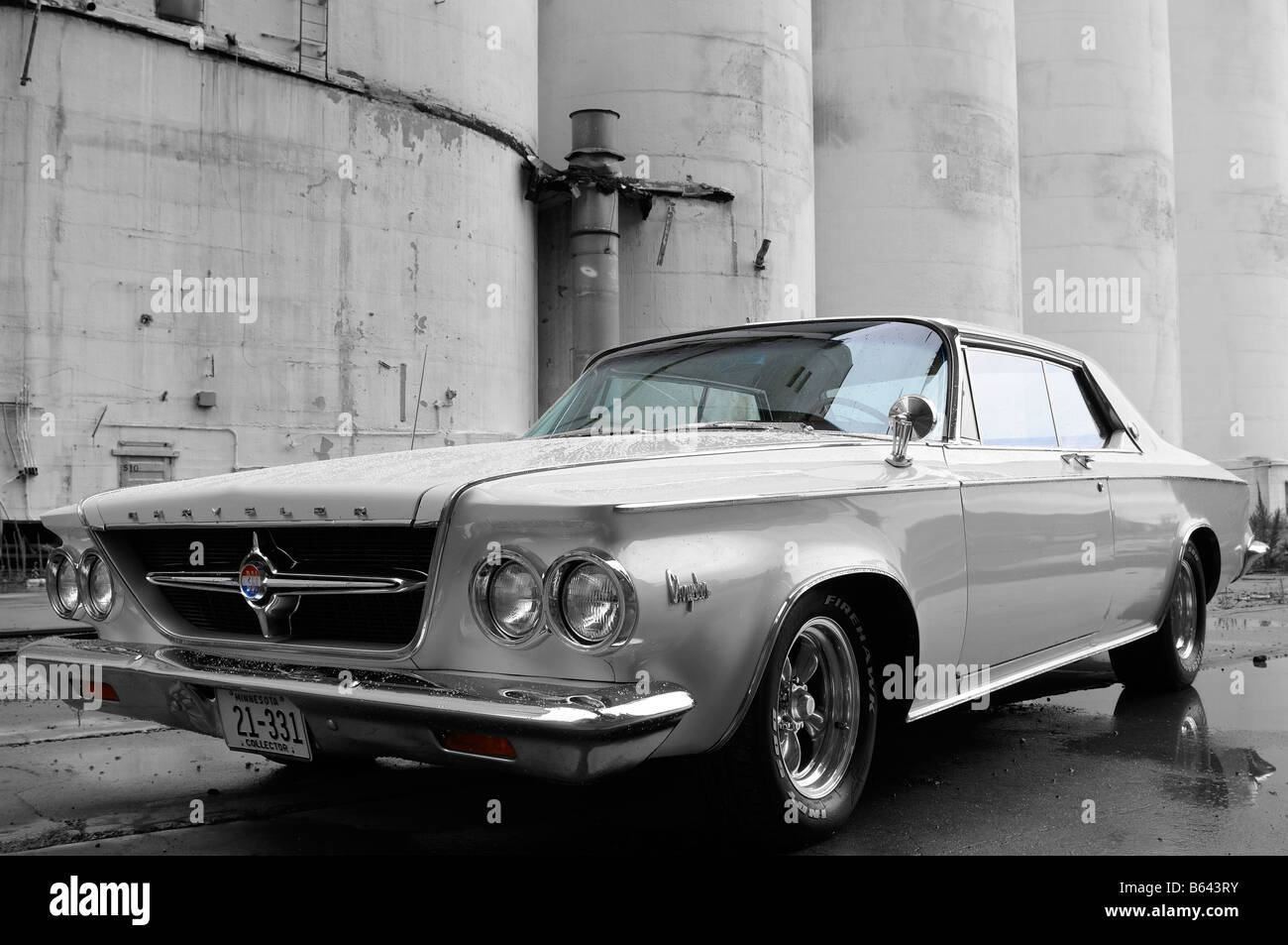 1963 Chrysler 300 white two door classic car by industrial silos monochrome - Stock Image